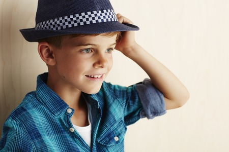checked shirt: Young boy wearing checked shirt and hat Stock Photo