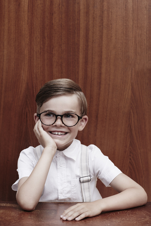 Portrait of young boy in hat and glasses, smiling photo