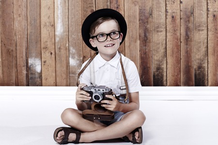wearing sandals: Young boy sitting on floor with camera