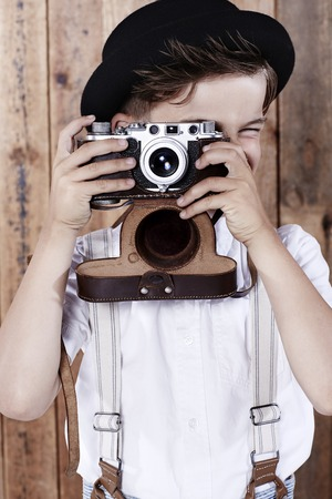 Young boy taking photograph with old camera photo