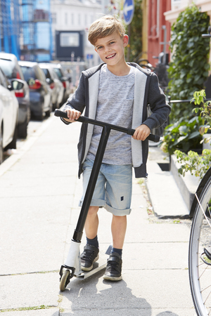 casual hooded top: Portrait of young boy with scooter on sidewalk Stock Photo
