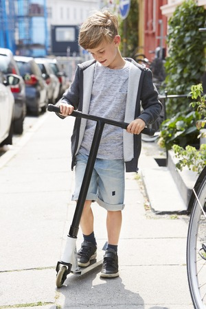 casual hooded top: Young boy looking down at scooter on sidewalk