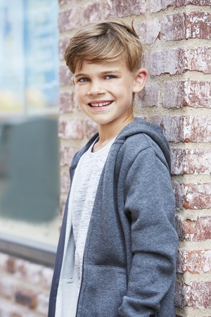 casual hooded top: Young boy leaning against wall, portrait