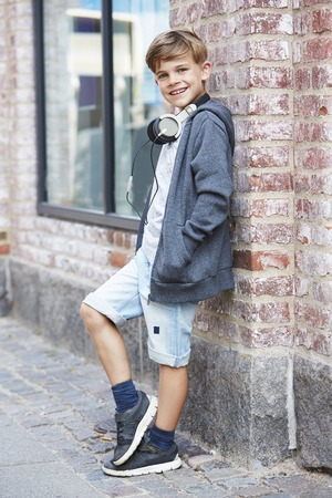 Young boy wearing headphones against wall, portrait Standard-Bild