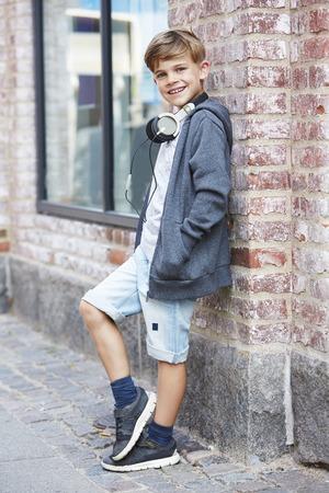 Young boy wearing headphones against wall, portrait Standard-Bild