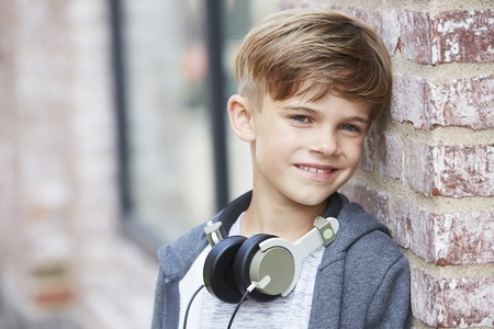 casual hooded top: Young boy wearing headphones, close up Stock Photo