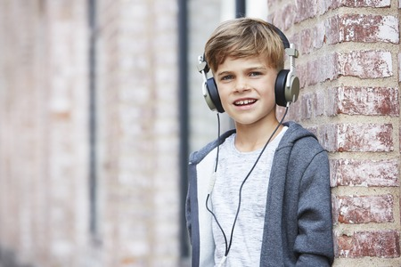 casual hooded top: Young boy wearing headphones, portrait