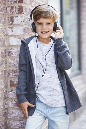 casual hooded top: Chico joven el uso de auriculares, retrato