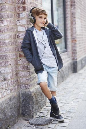 casual hooded top: Muchacho joven que se inclina contra la pared y el uso de auriculares