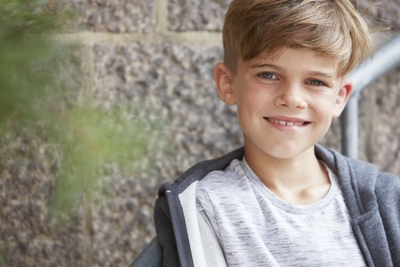 casual hooded top: Portrait of young boy smiling at camera, outdoors