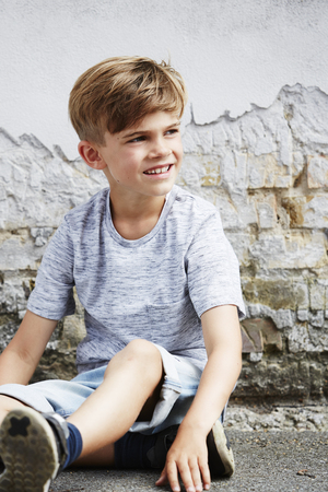 sitting on the ground: Young boy sitting on ground, looking away Stock Photo