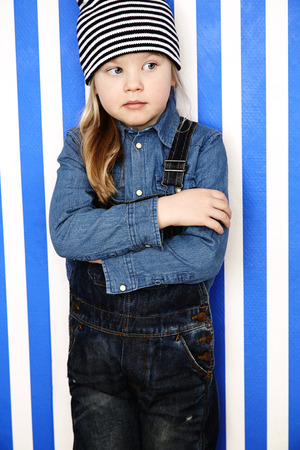 wooly: Young girl in striped hat and dungarees with arms folded