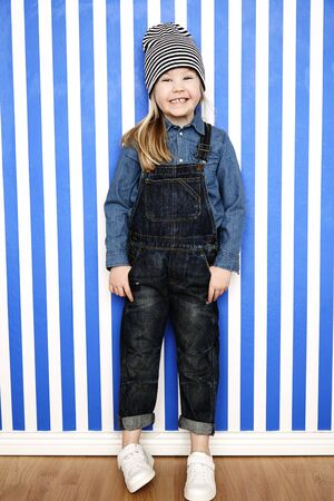 dungarees: Young girl in striped hat and dungarees, grinning