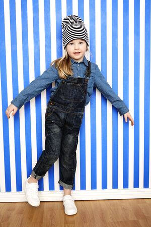 wooly: Young girl in striped hat and dungarees posing