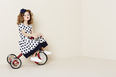 blonde girls: Young girl in spotty dress riding tricycle, portrait