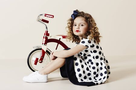 tricycle: Retro girl in spotty dress with tricycle, portrait