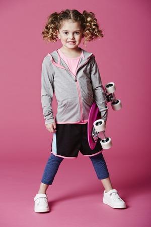 casual hooded top: Chica joven que sonr�e con el pat�n