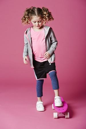 casual hooded top: Muchacha fresca en patineta en el estudio de color rosa Foto de archivo