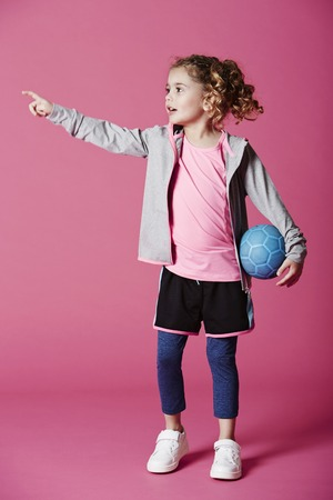 casual hooded top: Young girl in sportswear with soccer ball