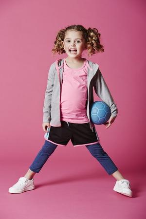 casual hooded top: Chica joven feliz que presenta con el bal�n de f�tbol
