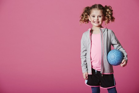 casual hooded top: Happy young girl holding blue football Stock Photo