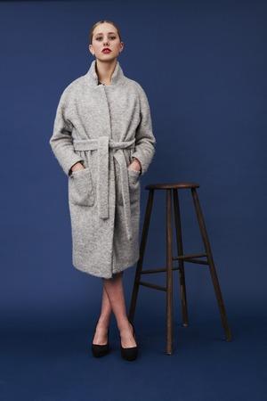18 19 years: Portrait of young woman in gray coat, studio