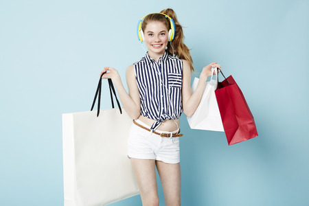 retail therapy: Portrait of fashionable teen with shopping bags