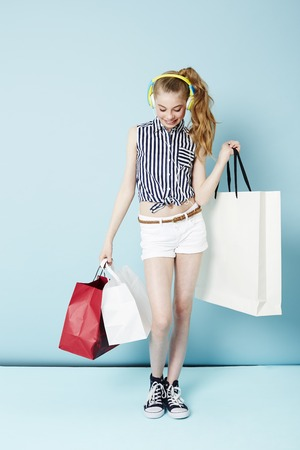 retail therapy: Teenage girl living to shop in studio Stock Photo