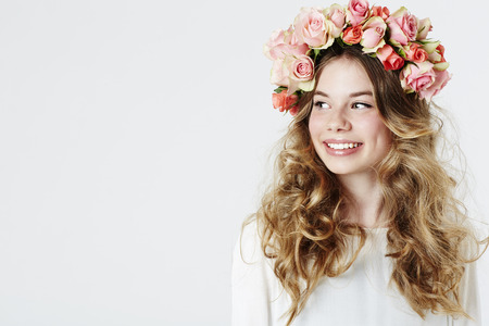 Smiling teenage girl wearing flowers,  studio