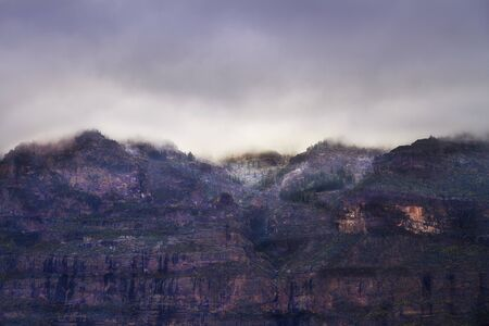 cliff face: Dramatic cliff face under cloudy sky Stock Photo