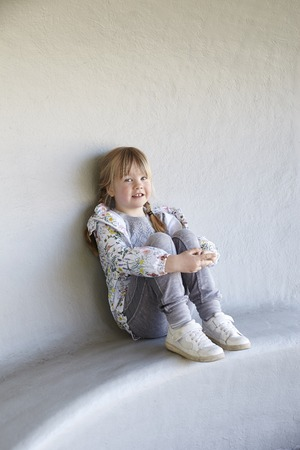 hugging knees: Portrait of young girl sitting outside Stock Photo