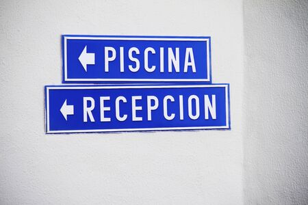 western script: Blue Spanish resort signs on white wall