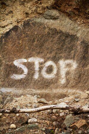 western script: Stop graffiti onto rock