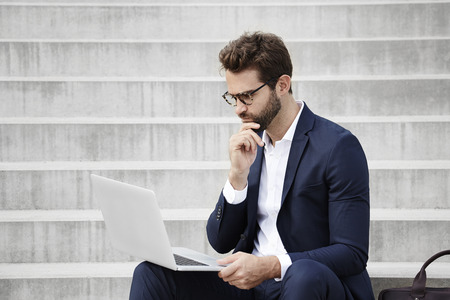 open collar: Businessman thinking over laptop on steps