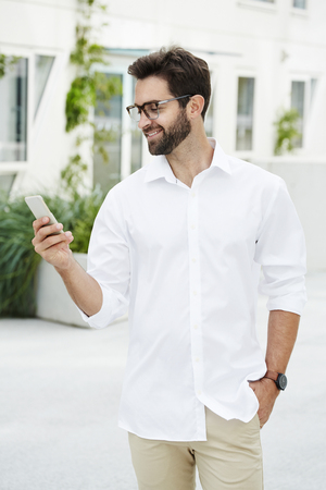 open collar: Guy texting on Smartphone and smiling