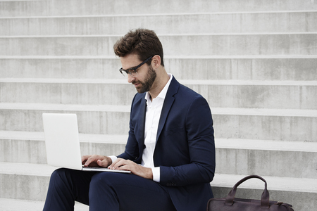 steps and staircases: Businessman working on laptop, sitting on steps