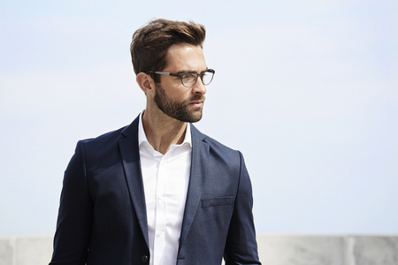 open collar: Bearded businessman looking away in spectacles