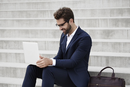 open collar: Businessman using laptop on steps Stock Photo