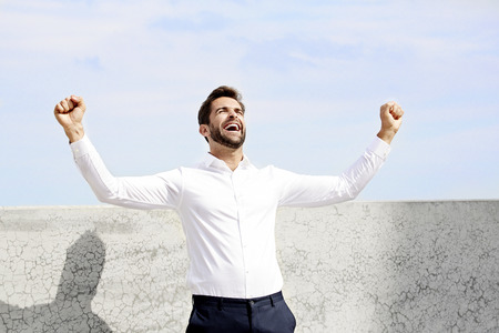 Businessman cheering in white shirt