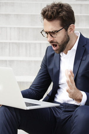 open collar: Shocked businessman using laptop