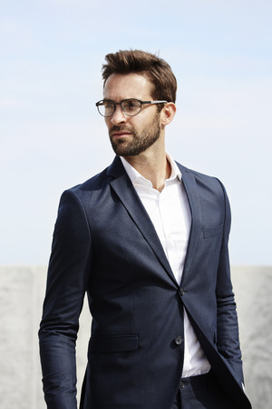 open collar: Serious businessman looking away in spectacles