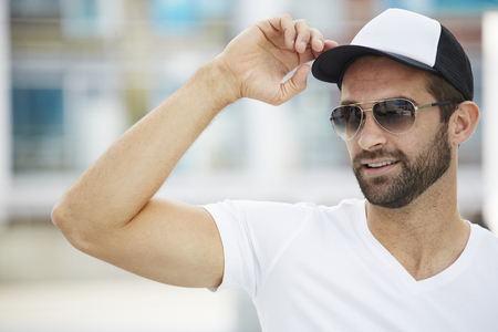 Man with glasses and beard adjusting cap