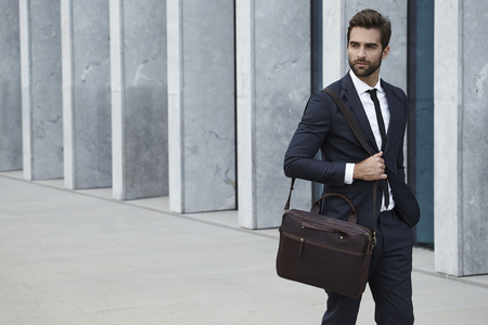Businessman with briefcase walking in city