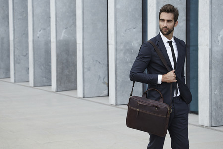 three day beard: Businessman with briefcase walking in city
