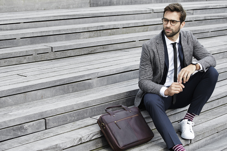 steps and staircases: Businessman sitting on steps, looking away Stock Photo