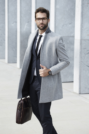 Serious and suited businessman with case Stock Photo