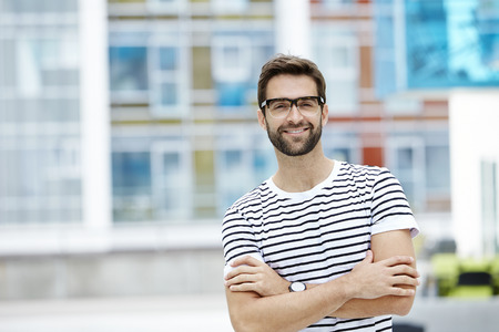 bespectacled man: Bespectacled and confident man in striped t-shirt Stock Photo