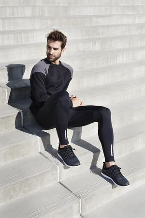 steps and staircases: Athlete in black sportswear sitting on steps