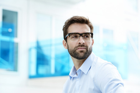 Serous man with stubble and glasses
