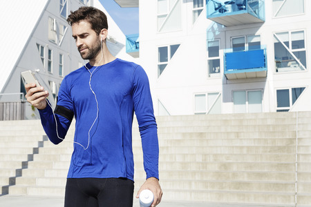 Athlete with music player in urban environment Stock Photo